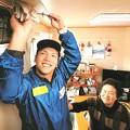 写真: 兵庫県から登米市を訪れ、仮設住宅のエアコンを掃除するボランティアの男性(左)