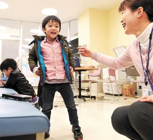 写真: 飛翔ちゃんの成長を喜ぶ阿部さん(右)。再会した飛翔ちゃんは、ひらがなで名前を書けるようになっていた=昨年12月21日、石巻市